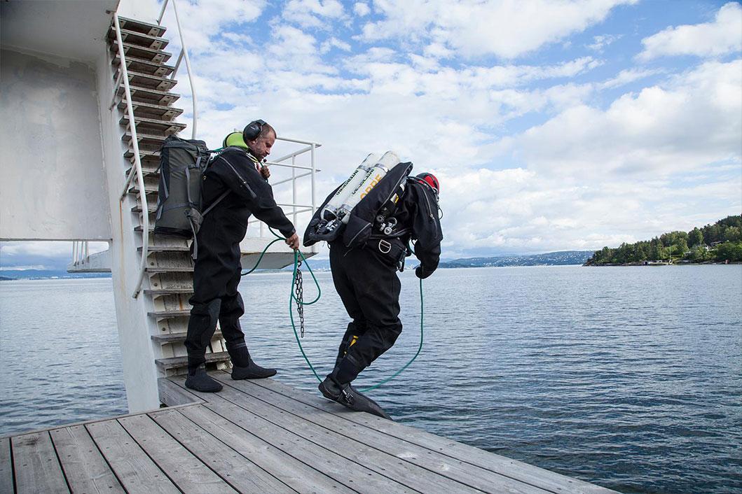 En dykker hopper uti vannet for å lete etter rusk.