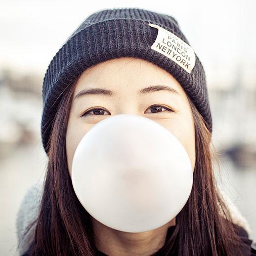 Jente blåser tyggegummi-bobler