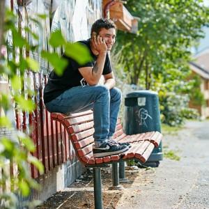 Gutt snakker i telefonen mens han sitter på en benk i det grønne byrommet i Oslo